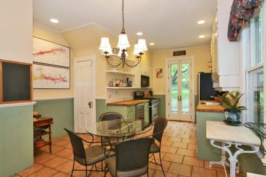 Sun drenched, eat in kitchen with door to patio and private, park like grounds