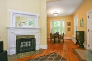 Inviting living room fireplace provides for cozy nights. Open floor plan flows nicely into full dining room. Original pine floors and details offers the best of both worlds.